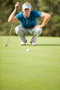 Man preparing to putt on golf courseの写真素材 [FYI02156157]