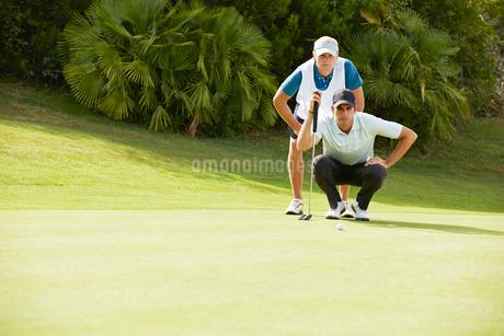 Caddy and golfer preparing to puttの写真素材 [FYI02156196]