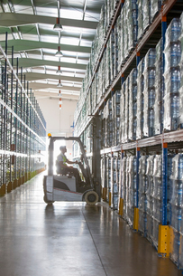 Worker operating forklift in warehouseの写真素材 [FYI02156214]