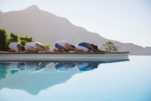 People practicing yoga at poolsideの写真素材 [FYI02156294]