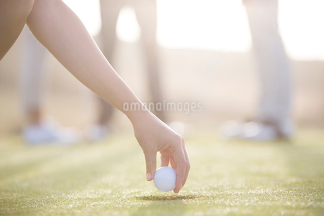 Woman teeing golf ball on courseの写真素材 [FYI02156331]