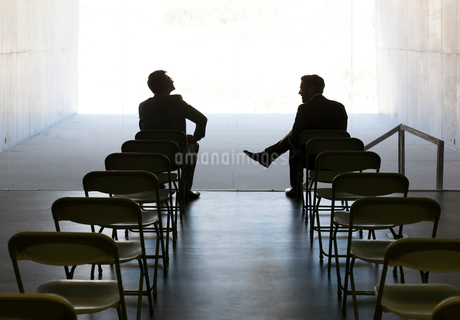 Businessmen talking at chairs in a rowの写真素材 [FYI02156459]