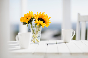 Vase of flowers and coffee cups on kitchen tableの写真素材 [FYI02156463]