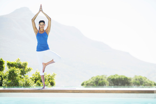 Woman practicing yoga at poolsideの写真素材 [FYI02156471]