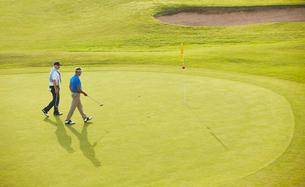 Senior men walking toward flag and hole on golf courseの写真素材 [FYI02156536]