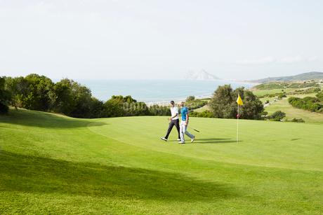 Men walking on golf course overlooking oceanの写真素材 [FYI02156549]