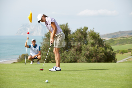 Caddy watching woman putt on golf courseの写真素材 [FYI02156550]