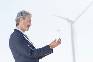Businessman examining glass of water by wind turbineの写真素材 [FYI02156726]