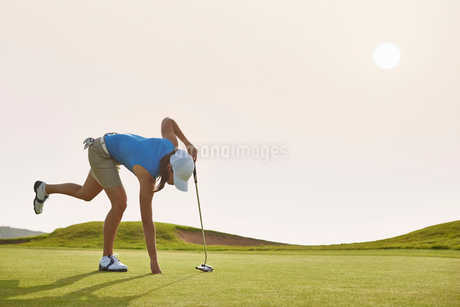 Woman reaching for ball in hole on golf courseの写真素材 [FYI02156759]