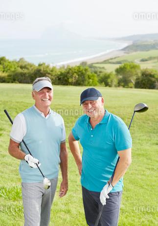 Senior men smiling on golf course overlooking oceanの写真素材 [FYI02156765]