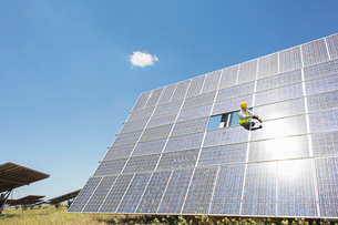 Worker examining solar panel in rural landscapeの写真素材 [FYI02156801]