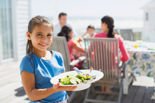 Girl holding salad on sunny patioの写真素材 [FYI02156867]