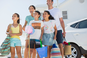 Family standing with beach gear in sunny drivewayの写真素材 [FYI02156923]