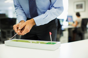 Businessman playing with toy golf set in officeの写真素材 [FYI02156992]