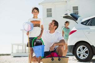 Father and son holding beach gear outside car in sunny drivewayの写真素材 [FYI02157131]
