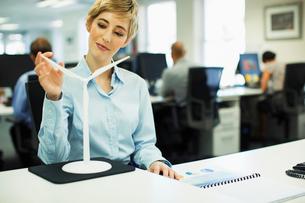 Businesswoman examining toy wind turbine in officeの写真素材 [FYI02157142]
