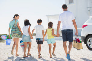 Family holding hands and carrying beach gear in sunny drivewayの写真素材 [FYI02157149]