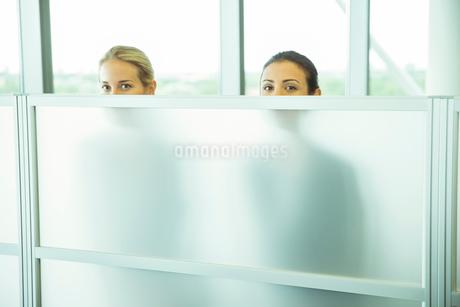 Businesswomen peeking over half wall in officeの写真素材 [FYI02157153]