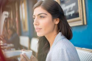 Woman drinking espresso at sidewalk cafeの写真素材 [FYI02157404]