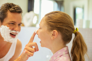 Father and daughter playing with shaving cream in bathroomの写真素材 [FYI02157463]