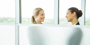 Businesswomen talking behind half wall in officeの写真素材 [FYI02157549]