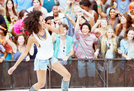 Fans cheering for performer singing on stage at music festivalの写真素材 [FYI02157572]