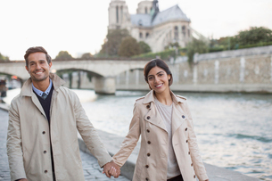 Couple holding hands along Seine River near Notre Dame Cathedral, Paris, Franceの写真素材 [FYI02157594]