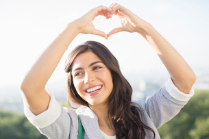 Woman making heart-shape with hands outdoorsの写真素材 [FYI02157631]