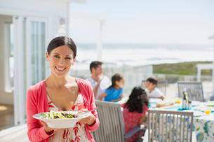 Woman holding salad bowl on sunny patio overlooking oceanの写真素材 [FYI02157671]