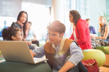 University student using laptop in loungeの写真素材 [FYI02157706]