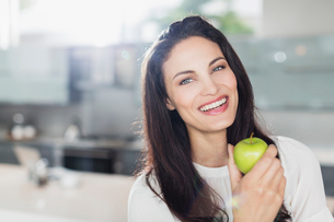 Portrait of smiling woman eating apple in kitchenの写真素材 [FYI02157713]
