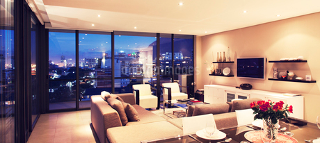 Illuminated modern living room overlooking cityの写真素材 [FYI02157726]
