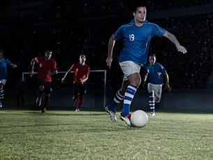 Soccer players chasing ball on fieldの写真素材 [FYI02157815]