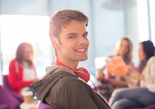 Smiling university student wearing headphones in loungeの写真素材 [FYI02157820]