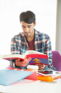 University student reading textbook in loungeの写真素材 [FYI02157960]