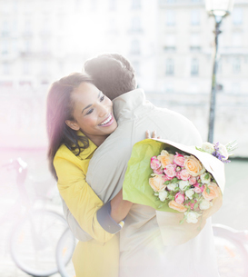 Couple with bouquet of flowers hugging along Seine River, Paris, Franceの写真素材 [FYI02158001]