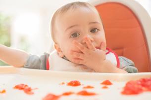Baby boy eating gelatin dessert in high chairの写真素材 [FYI02158056]