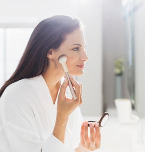 Woman in bathrobe applying makeup in bathroomの写真素材 [FYI02158167]