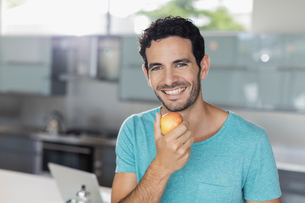 Portrait of smiling man eating apple in kitchenの写真素材 [FYI02158217]