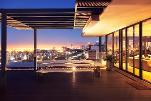 Illuminated luxury house and patio overlooking cityの写真素材 [FYI02158247]