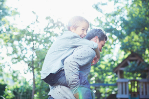 Father carrying son piggyback outdoorsの写真素材 [FYI02158294]