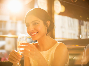Well-dressed woman drinking champagne in restaurantの写真素材 [FYI02158355]