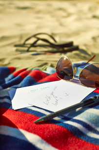 Postcards, sunglasses and sandals at beachの写真素材 [FYI02158439]