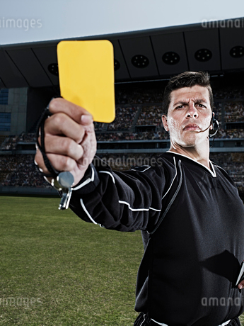Referee flashing yellow card on soccer fieldの写真素材 [FYI02158444]