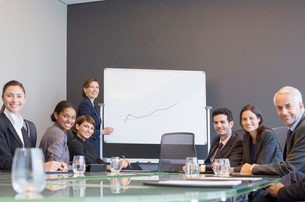 Businesswoman drawing graph for colleagues in meetingの写真素材 [FYI02158574]