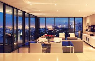 Illuminated modern living room overlooking cityの写真素材 [FYI02158575]