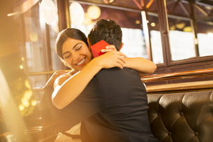 Woman with jewelry box hugging man in restaurantの写真素材 [FYI02158661]