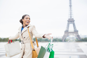 Woman carrying shopping bags by Eiffel Tower, Paris, Franceの写真素材 [FYI02158673]