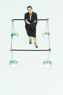 Businesswoman standing in roped-off squareの写真素材 [FYI02158699]