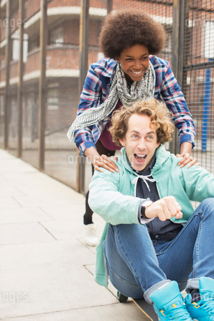 Couple playing on skateboard on city streetの写真素材 [FYI02158754]